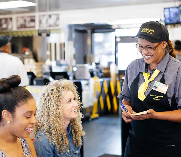 Smiling Waffle House employee taking orders
