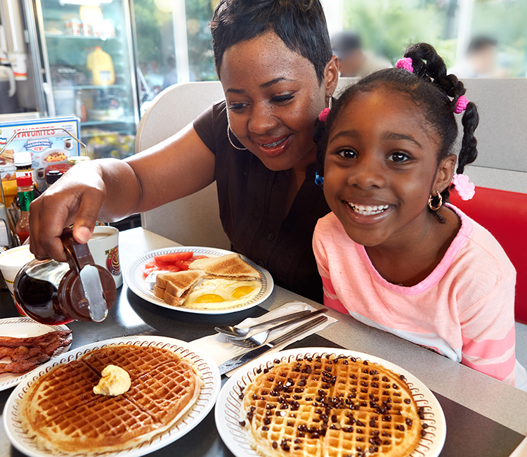 Mother and daughter enjoying a waffle house breakfast