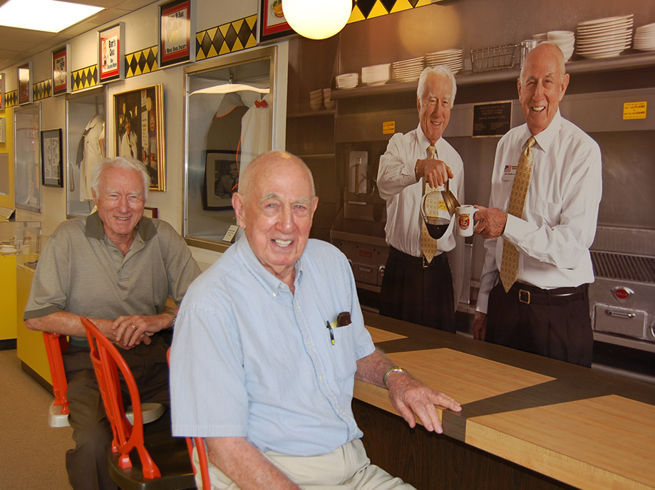 Joe Rogers Sr and Tom Forkner sitting in front of a print of their photo